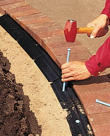 To install a brick border, lay bricks on a compacted bed of gravel and sand. Lock them in place with plastic edging.