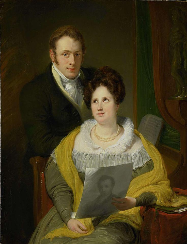 Jan Willem Pieneman | Portrait of a Woman and a Man, Jan Willem Pieneman, 1829 | Portret van een dame en een heer in een interieur. Met de linkerarm leunt zij op een tafeltje waarop een portefeuille ligt en houdt een getekend portret van een man in haar hand. De man staat achter haar, leunend op de stoel.