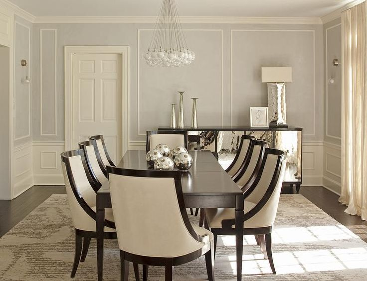 Elegant dining room features top part of walls painted pale gray lined with decorative trim moldings and bottom part of wall clad in wainscoting lined with a mirrored buffet cabinet accented with dark wood trim.