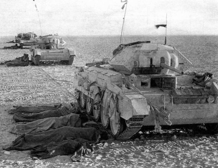 British tank crews resting in the shade of Crusader tanks (2 pdr variant) in the Western Desert of North Africa, 1941.  Crusaders were fast but unreliable.