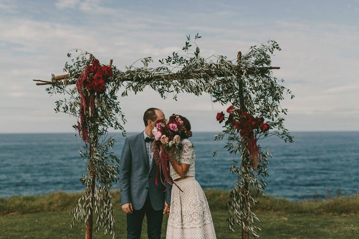 Pink, peach and plum bridal bouquet, olive leaf wedding arch and hair circlet by Shady Fig using David Austin roses, peony roses, tulips, peppercorn and amarnthus. Photographed by Zoe Morely