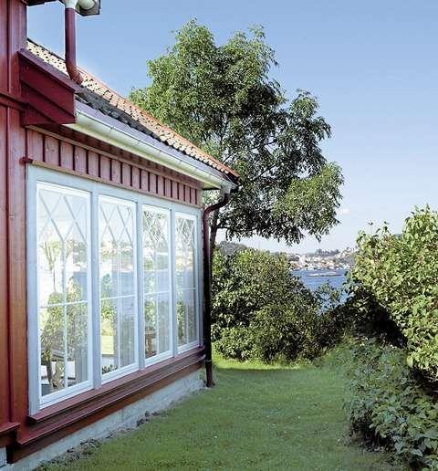 Gotisk inspirert: Det er brukt gammel tegelstein på taket, lys grå belistning. Sprossevinduer er gotiskinspirert med mønsterinndeling av vindusflatene