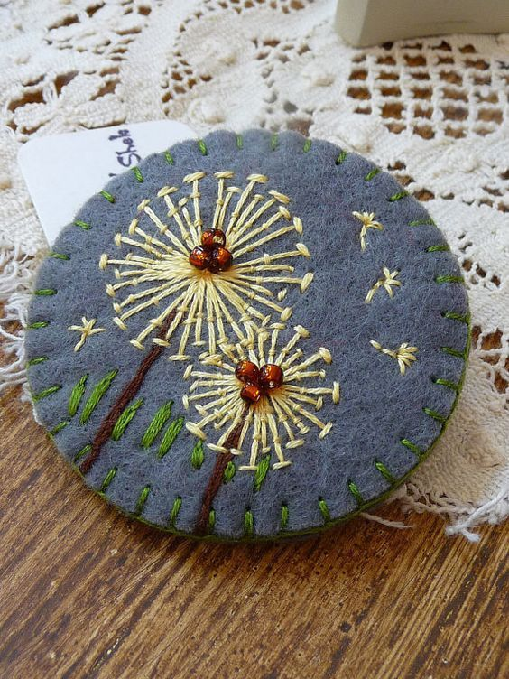 Dandelion. The flower is embroidered on felt with straight stitches and few beads have been added to depict the center of the flower.: