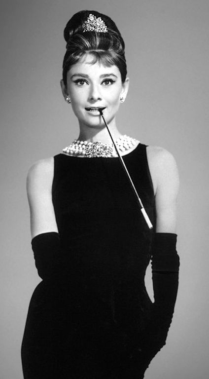 Audrey Hepburn in a black, shoulderless dress, matching gloves and a tiara, smiling with a cigarette holder in her mouth as Holly Golightly in 'Breakfast at Tiffany's,' directed by Blake Edwards, New York, New York, 1961.