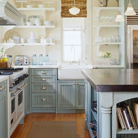 A farmhouse sink sits center stage in this cottage-style kitchen. White countertops, pearl-gray beaded-board cabinets and open shelving above the apron sink create a clean look with everything for a great meal right at hand.