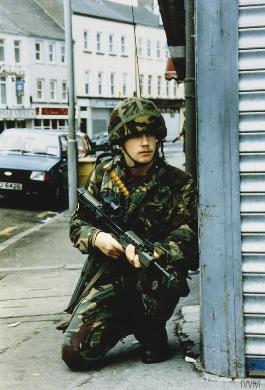 A British soldier kneels at a street corner during a patrol in Newry, County Down. Note the handle of a baton sticking out the top of his tunic.