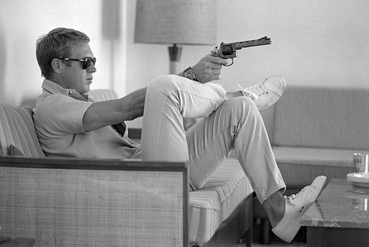 Photos of the legendary Steve McQueen riding motorcycles, camping, working out and shooting guns in the desert with his wife in 1963.