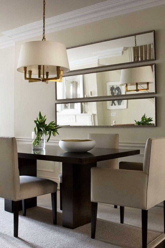 Comedor con tres espejos rectangulares de marco delgado de madera, dispuestos de manera horizontal en el muro y frente a la mesa.