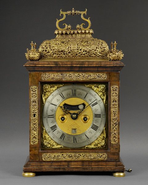 James Markwick  1697 A fine William and Mary quarter repeating spring table clock veneered with olivewood. The flamboyant case stands on brass bun feet with repoussé mounts to the door and a repoussé basket top supporting the carrying handle. The basket is flanked to the four corners with unusual four leaf finials.  The 7 in (18 cm) square dial is mounted with wing cherub spandrels and silvered chapter ring with strike/silent option above. There is a false pendulum aperture, ringed winding…