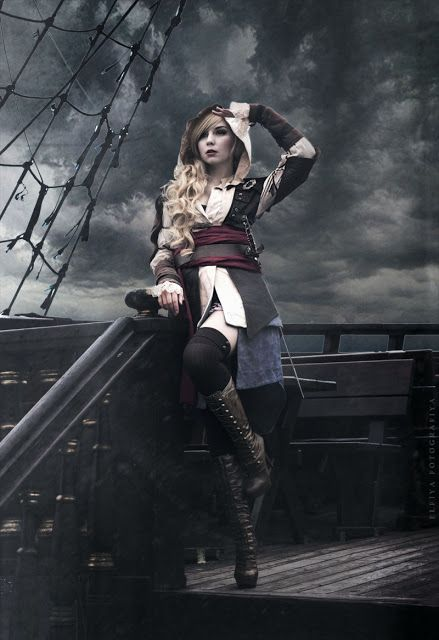 Female Steampunk Pirate (or lady pirate) - Girl wearing hooded shirt dress, jacket, knee socks, victorian lace up boots, red sash and a belt. Edward Kenway - Assassin's Creed - For costume tutorials, clothing guide, fashion inspiration photo gallery, calendar of Steampunk events, & more, visit SteampunkFashionGuide.com