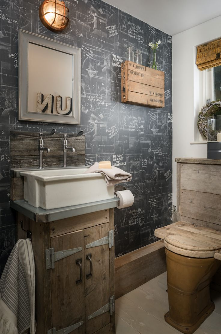 Chalkboard style wallpaper and reclaimed wood accents in this 1/2 bath give it unusual industrial-meets-rustic charm.