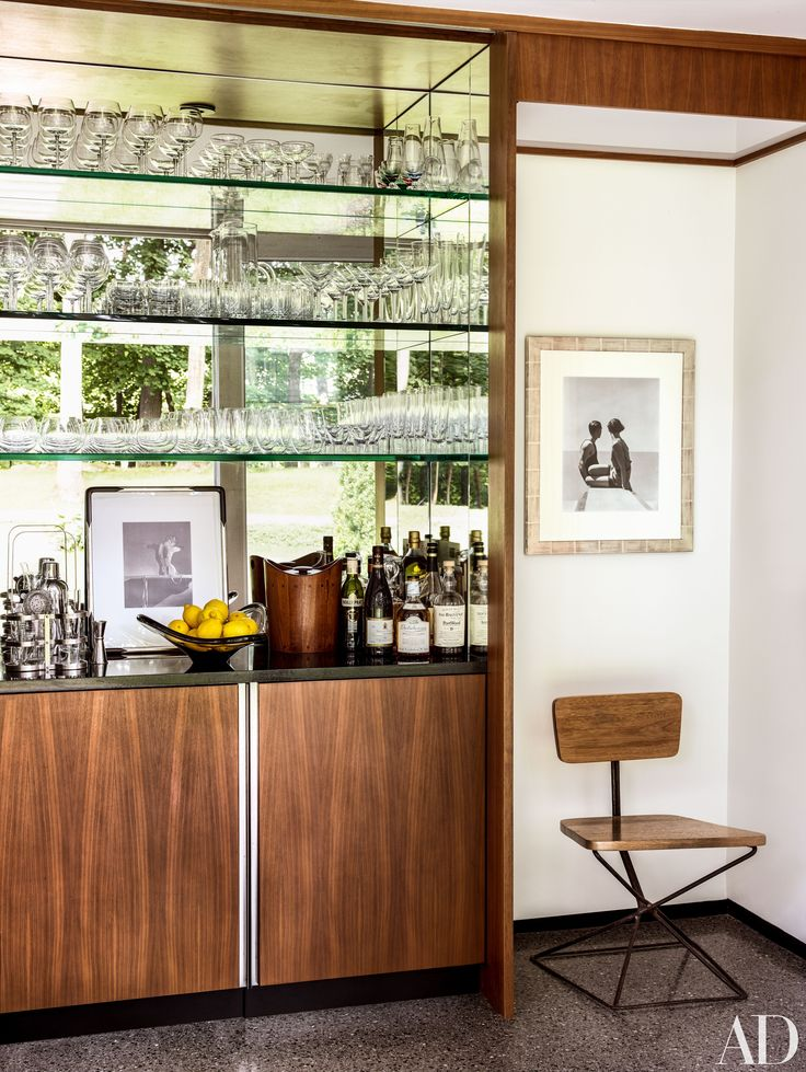 Iconic photographs by Horst P. Horst and George Hoyningen-Huene are displayed in the entry's bar area of a midcentury home.