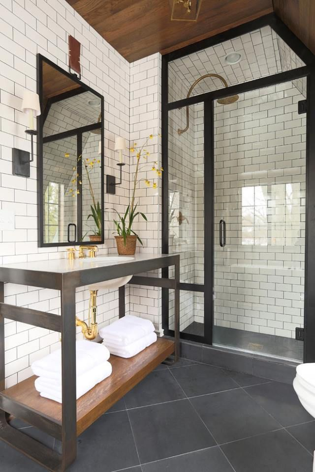 shower with white subway tile, black trim, wood accents