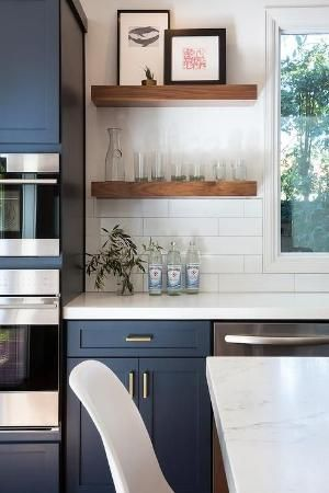 Fantastic kitchen features navy blue shaker cabinets adorned aged brass pulls paired with white quartz countertops that resemble marble and a white stacked tile backsplash. by Shelly Raquel