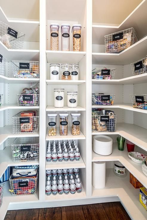 White u-shaped kitchen pantry boasts white modular shelves stocked with labeled wire snack baskets and cereal canisters.