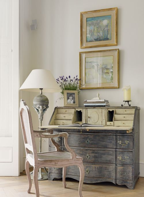 vignette featuring antiques and stacked art on top of wonderful blue Swedish desk...