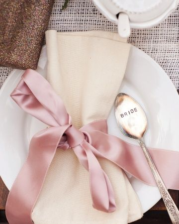 A spoon for the bride and an ivory napkin with a blush ribbon set a sweet scene