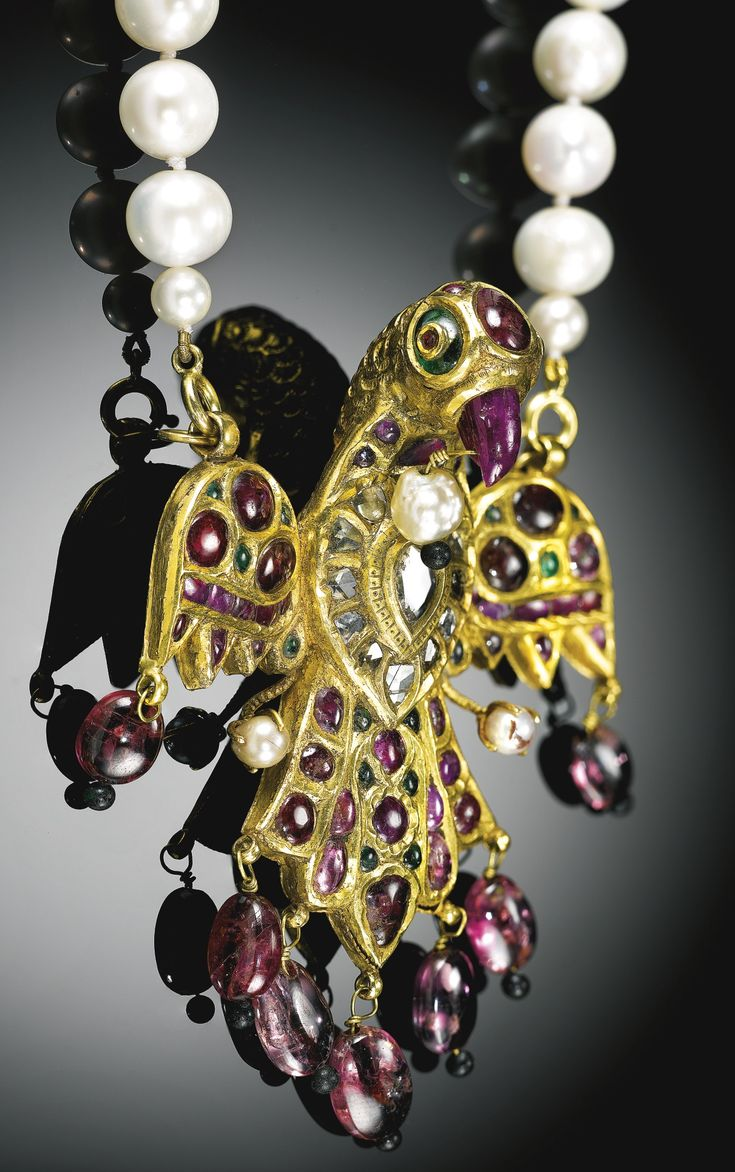 AN EAGLE-SHAPED GEM-SET PENDANT, INDIA, DECCAN, 18TH CENTURY, WITH LATER PEARL CHAIN in the form of an eagle with outstretched wings and tail feathers, the gold body set with rubies and emeralds, featuring a lasque-cut diamond medallion on the breast, the ruby beak, wings and tail feathers with attached drop-pendant pearls and rubies, the reverse incised with plumage details, loops attaching later pearl suspension chain