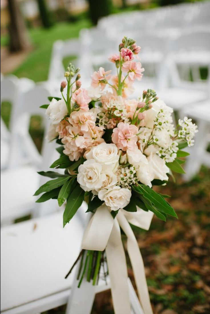 pretty pew marker of peach stock, white majolik spray roses, white wax flower and bay leafy tied with a cream satin ribbon dress the aisle of the wedding ceremony