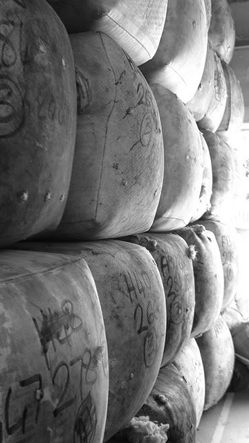 Part of a load of wool waiting to go out for processing. The numbers scrawled on each 275kg (roughly) bale identify the grade of wool, as well as the local wool grower it came from. These identifiers stay with the wool right through all stages of the process, both electronically and in huge marker pen, so we know who and where it came from.