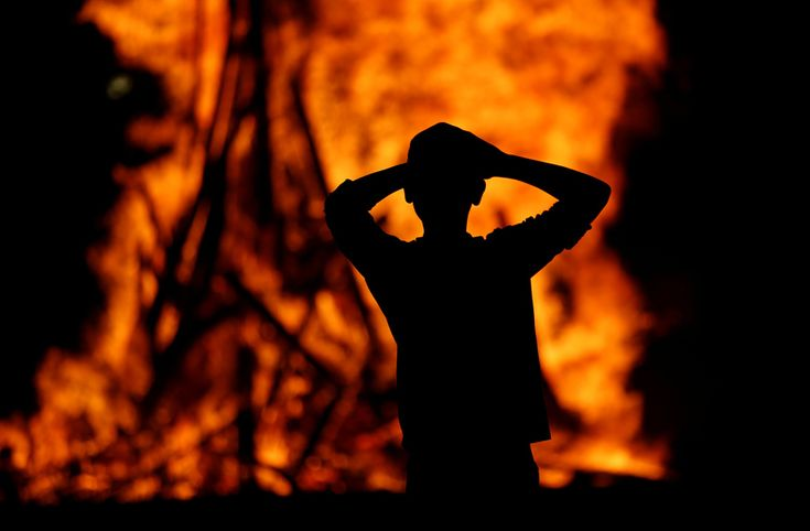 An Ultra-Orthodox Jewish boy stands around a bonfire as he celebrates the Jewish holiday of Lag Ba'Omer in the city of Ashdod, Israel, on May 25, 2016. Amir Cohen / Reuters