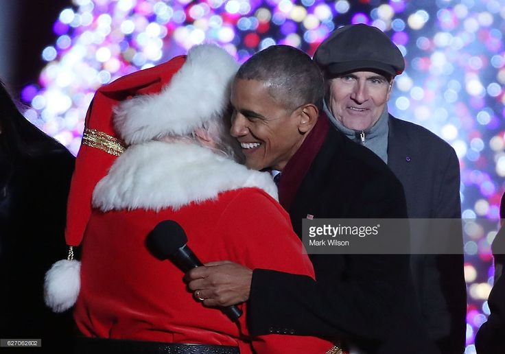 U.S. President Barack Obama gets a hug from Santa Claus as musician James Taylor looks on during the National Christmas Tree lighting ceremony, on December 1, 2016 in Washington, DC. This year is the 94th annual National Christmas Tree Lighting Ceremony.