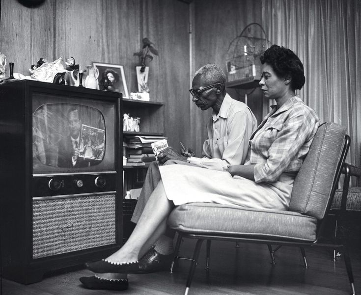 """Mrs. L.C. Bates, president of the Arkansas chapter of the National Association for the Advancement of Colored People, and her husband watch Gov. Orval Faubus on television as he addresses the nation. He attacked the president for sending federal troops into Little Rock, accusing the administration of employing """"police state methods."""" Bates was an adviser to nine black high school students who attempted to enroll in Central High School."""