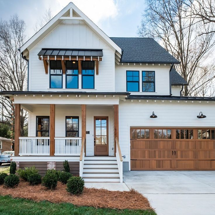 White modern home with wooden garage and lifted porch