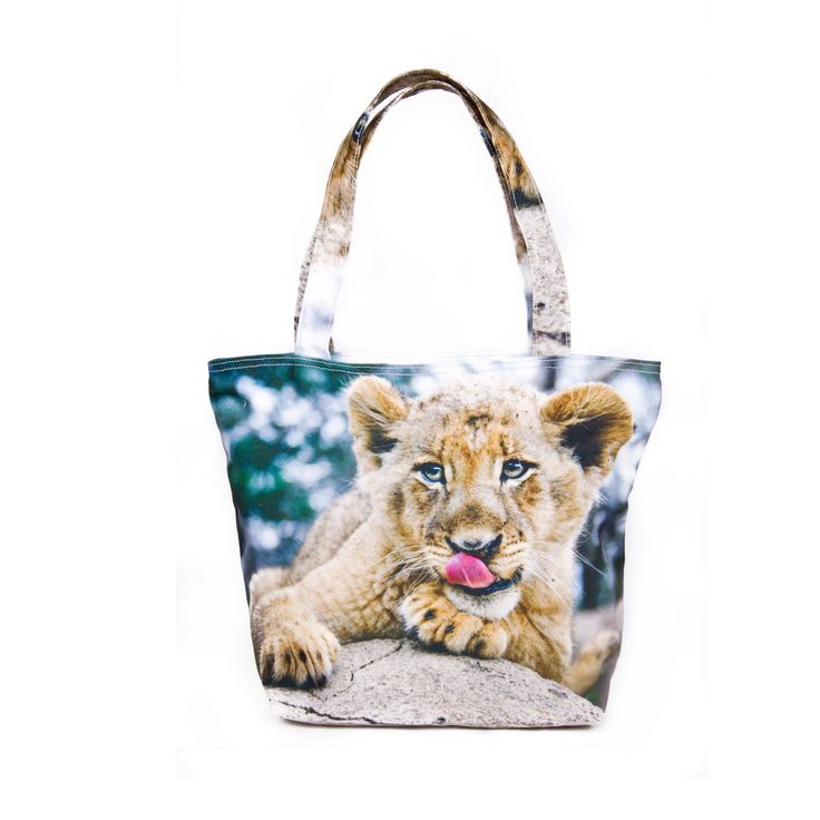 My Friend, Lion  .  Taking center stage is this adorable lion cub displaying its tongue playfully as it lays on a rock. This simple bag is cool and casual, the perfect piece for almost anything like those last minute errands. If you want a bag that brings a new definition of individuality then strike a pose with this adolescent feline.