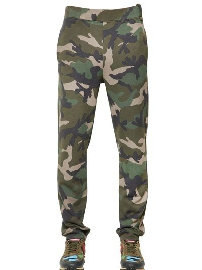 $890, Dark Green Camouflage Chinos: Valentino Camo Printed Cotton Jogging Pants. Sold by LUISAVIAROMA. Click for more info: https://lookastic.com/men/shop_items/257590/redirect