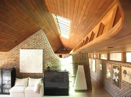 This architecturally-interesting 6-bed, 7-bath home features unusual swooping brick walls and this ship-like, wood-paneled ceiling in the living room.