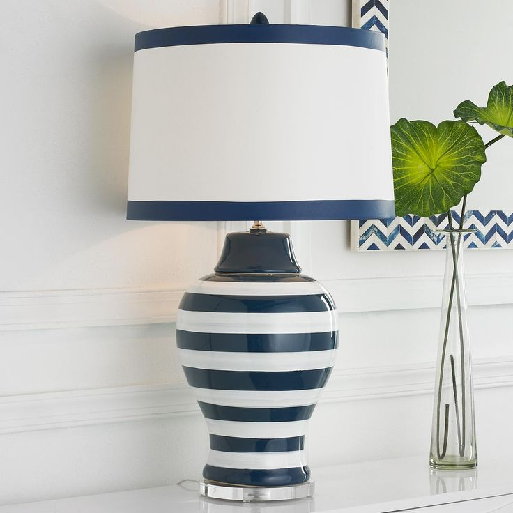 "Navy and White Stripe Table Lamp Navy blue and white stripes always add that classic chic touch to a room and this exclusive ceramic table lamp is done up just right with a clear plexi-glass base, flared white paper shade with navy trim and matching finial. 3-way 150 watts. (28""Hx15""W)"