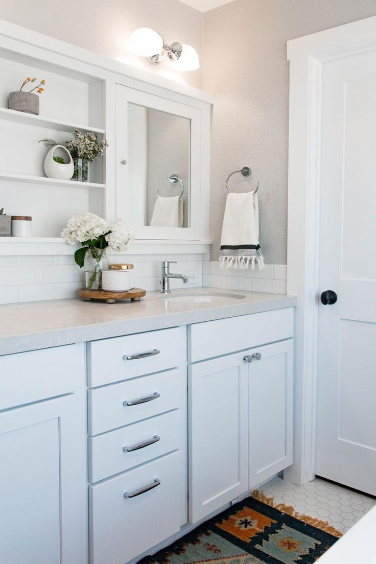 In a perfect match of the walls and molding, the double vanity features gray countertops accented by white cabinetry. Drawers, cabinets and shelves offer a place for anything and everything.