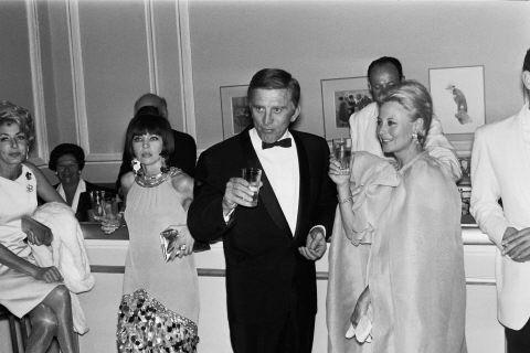 Finales de los 60, la moda cambia y los espectaculares vestidos de sirena dan paso a caftanes de inspiración folk, a trajes futuristas y a altos peinados.    En la imagen Leslie Caron, Kirk Douglas y Michèle Morgan.