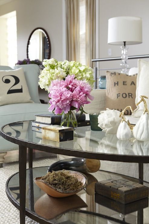source: Jillian Harris  Pastel living room with oval glass top cocktail table, blue accent chair, linen slipcover sofa and vintage grain sack pillows.
