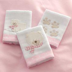 As Fraldinhas de boca são bordadas à mão com desenhos das Ursas Polar e suas pegadinhas com detalhes cor de rosa. Feitas em algodão, têm barra de tecido cor de rosa estampado com poás brancos, tema da coleção. São 03 unidades de 32 x 32 cm cada.