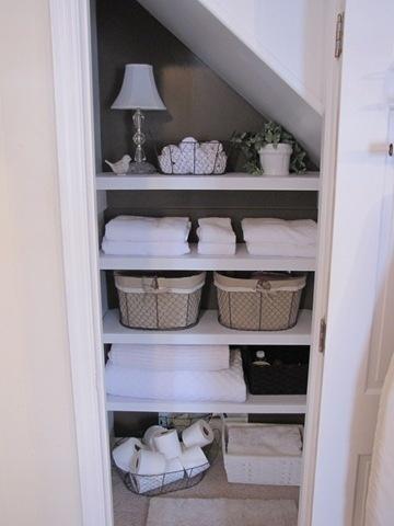 organized bathroom closet nook with painted shelves contrasting wall - Bathroom Closet Designs