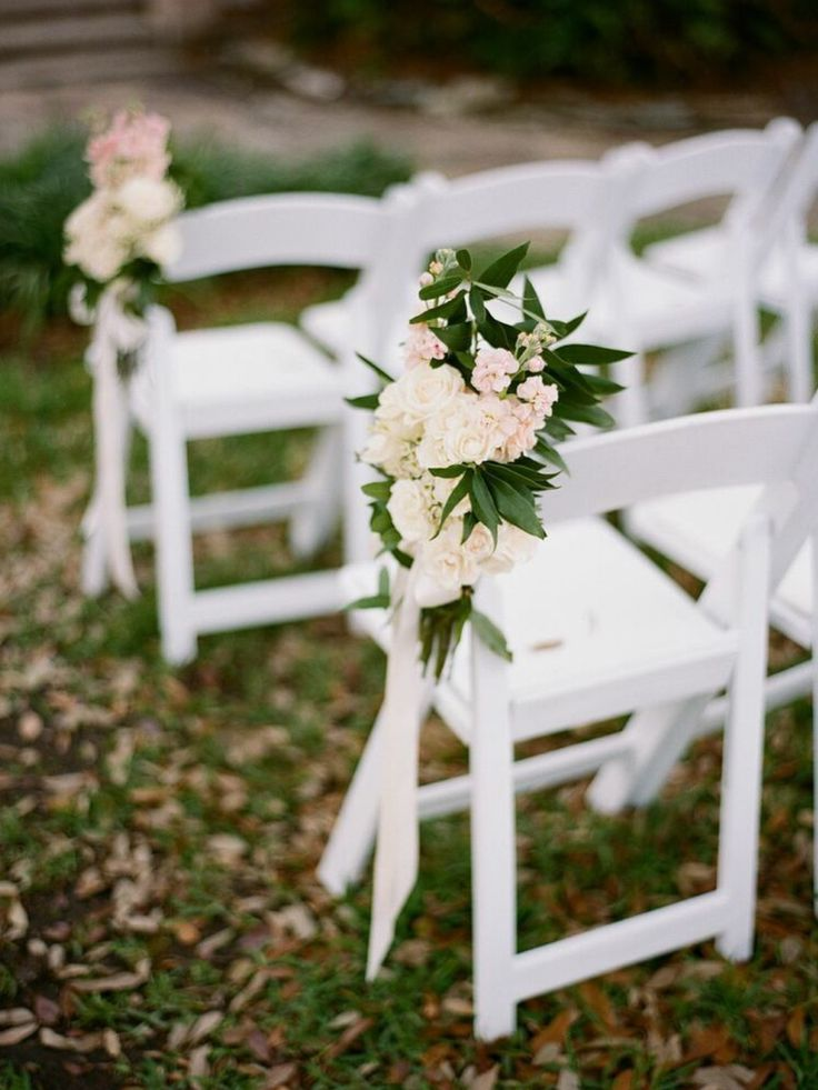 pretty pew markers of peach stock, white majolik spray roses, white wax flower and bay leafy tied with a cream satin ribbon dress the aisle of the wedding ceremony