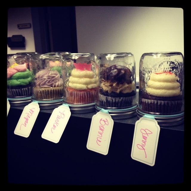 Cupcakes in upside down mason jars with personalized name tags for clients. I had to have help setting the cupcakes because they were so large... Make sure you get wide mouth mason jars if you do this! -- Cupcakes by Gigi's