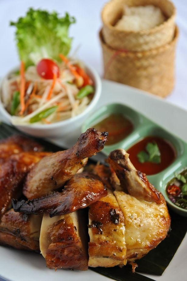 Kai Yang is a grilled half of chicken served with papaya salad and sticky rice from Tuk Tuk Thai Food Loft in Atlanta, GA.