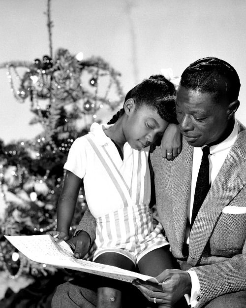 Nat King Cole with his daughter Natalie falling to sleep on his lap, c. 1955