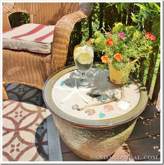 take a planters Pot/garden pot fill with sand and seashells and buy a glass table top and there you go DIY deck/patio table