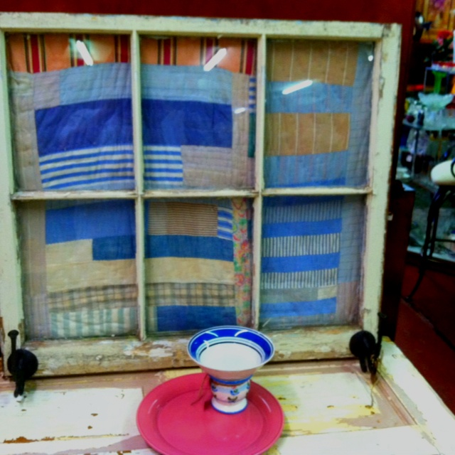 Old window sash coat rack with old quilt background ...