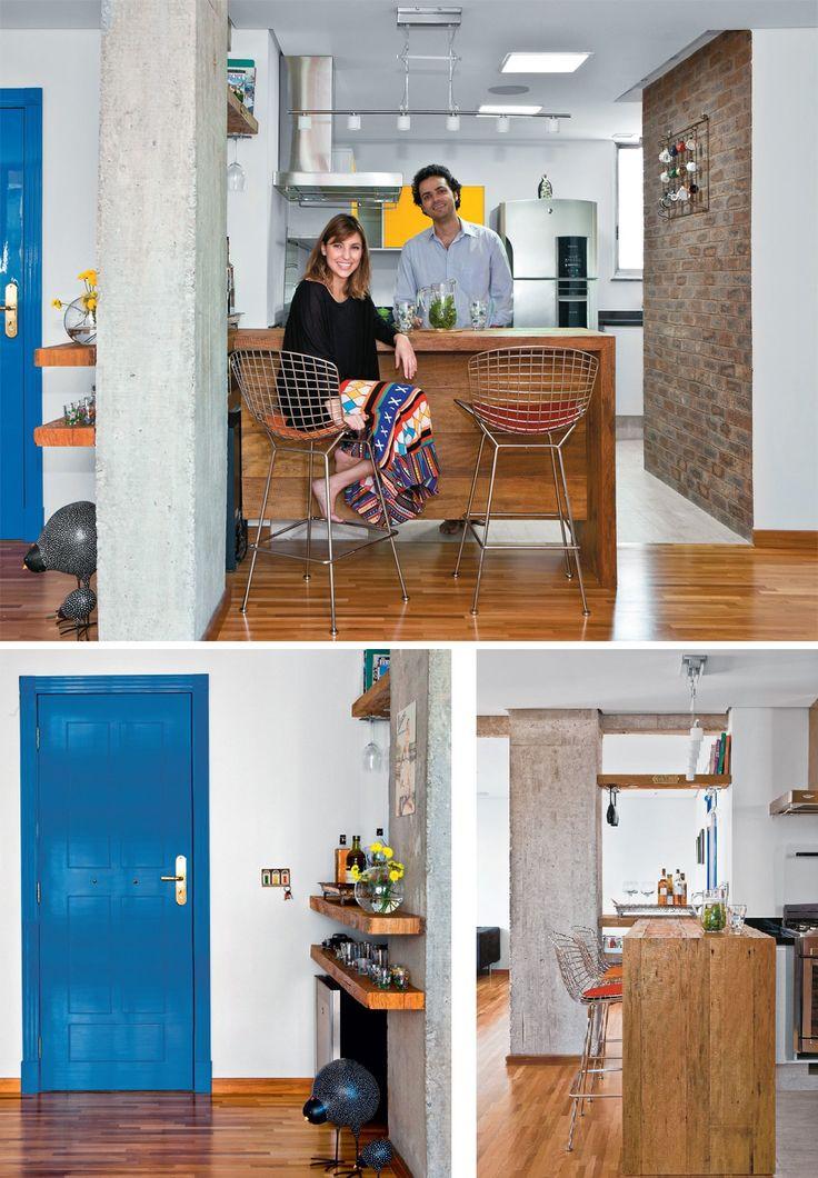 Na cozinha, o casal revestiu uma das paredes de tijolos. Laqueada, a porta social (Móveis Planejados Fartura, R$ 4 200) inspira-se no azul das portas de Dublin, Irlanda. Apenas um balcão de peroba-rosa de demolição, que mede 1,50 x 0,70 m e 1,10 m de altura, divide a cozinha da sala de estar e serve de apoio para as refeições. Trabalho da Móveis Planejados Fartura (que cobrou R$ 6 500). Na sala de estar, piso de tacos do tipo palito de madeira grápia (Pau-Pau).