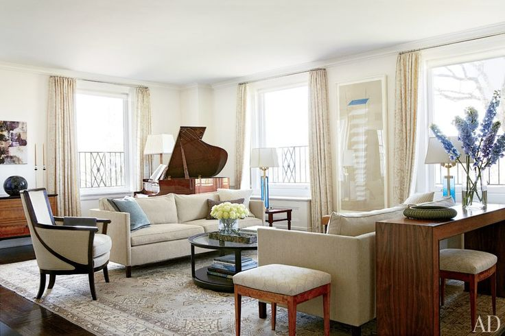 Designers Brooke Gomez and Mariette Himes Gomez updated Pollan and Fox's living room with clean-lined modern furnishings, including blue-glass table lamps from Bernd Goeckler Antiques and a pair of Dessin Fournir sofas covered in a Claremont fabric; the artwork between the windows is by Louise Bourgeois, the piano is by Steinway & Sons, and the early-20th-century Turkish Oushak carpet is from Doris Leslie Blau.