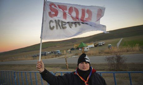 A protester holds a 'Stop Chevron' flag at a makeshift camp near the village of Pungesti, Romania, where the US firm wants to drill for shal...