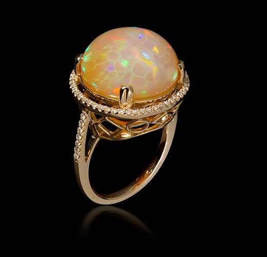 "Ethiopian Opal Ring | Heath London Jewelry and Gemstones - When we first heard about the new find of Ethiopian Welo Opal ring  from our Chang Mai dealer he said, ""Wait till you see these opals,  they're disco balls"".  He was right! The colors explode out of this delicate stone. -  Stone: Ethiopian Opal, 8.12cts, 15mm, Diamond accents -  Metal: 14kt Gold"