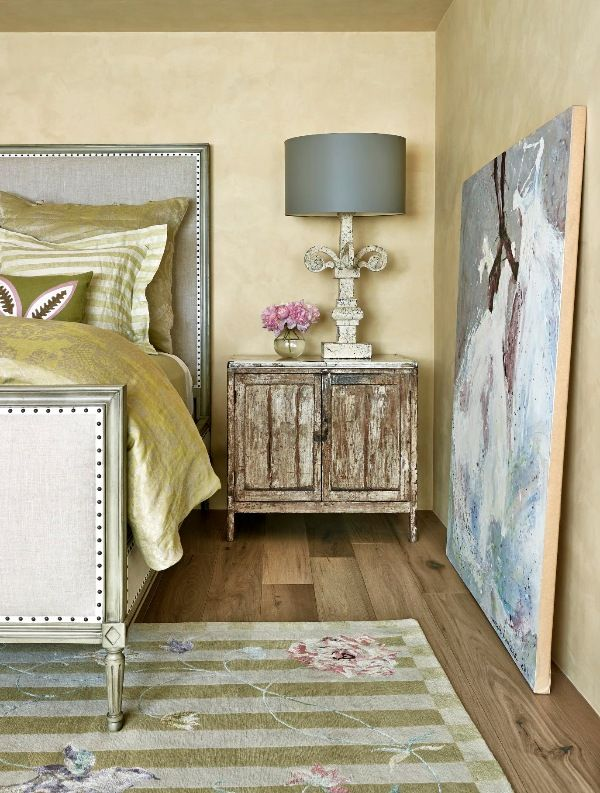 Rustic zinc-top chests serve as bedside tables in a guest room outfitted with a nailhead-trimmed bed and a lush silk rug. - Photo: Werner Segarra / Design: Suzanne Biers Harrington