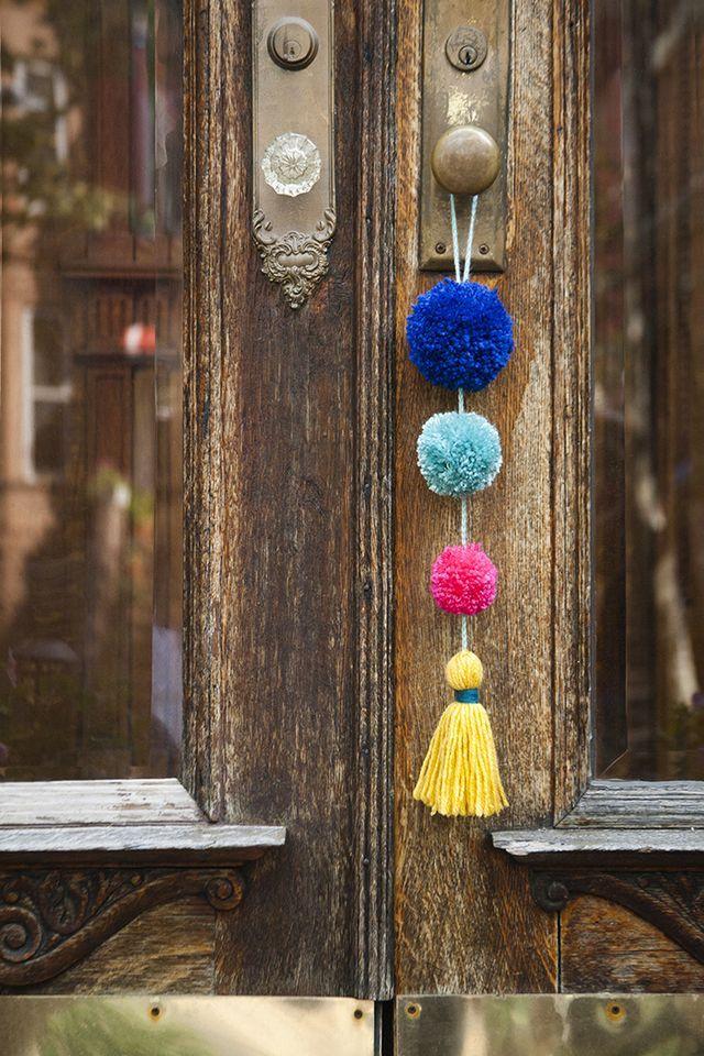 Pompons colorés accrochés à la poignée de porte