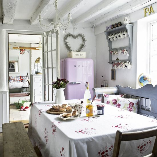"""White country kitchen-diner:  To create a country look in a white kitchen, delicate floral patterns, pink appliances and soft grey furniture are perfect. A box bench is a relaxed way to include a dining area into a kitchen, while a mix of furniture in differing materials brings an added rustic element.